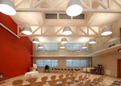 Veranstaltungsraum von Holzbau Aumann, große Pendelleuchten vor erhellter Holzdecke
