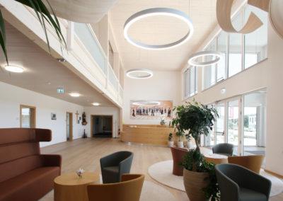 Foyer von Holzbau Aumann, Deckneleuchten im Flur mit Lichtkorona, Luftraum mit großen Lichtringen, Blick von der Lounge