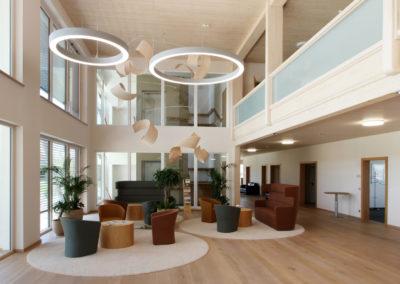 Foyer von Holzbau Aumann, Deckneleuchten im Flur mit Lichtkorona, Luftraum mit großen Lichtringen, Blick auf die Lounge