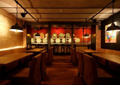 Blick in den Gastraum der Brauerei Maisl mit Beleuchtetem Fasslager im Hintergrund