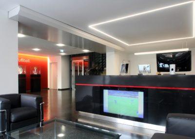 Empfang Olympiaverlag aus Sicht der Lounge mit Linearer Pendelleuchte und LED Linien in der Decke